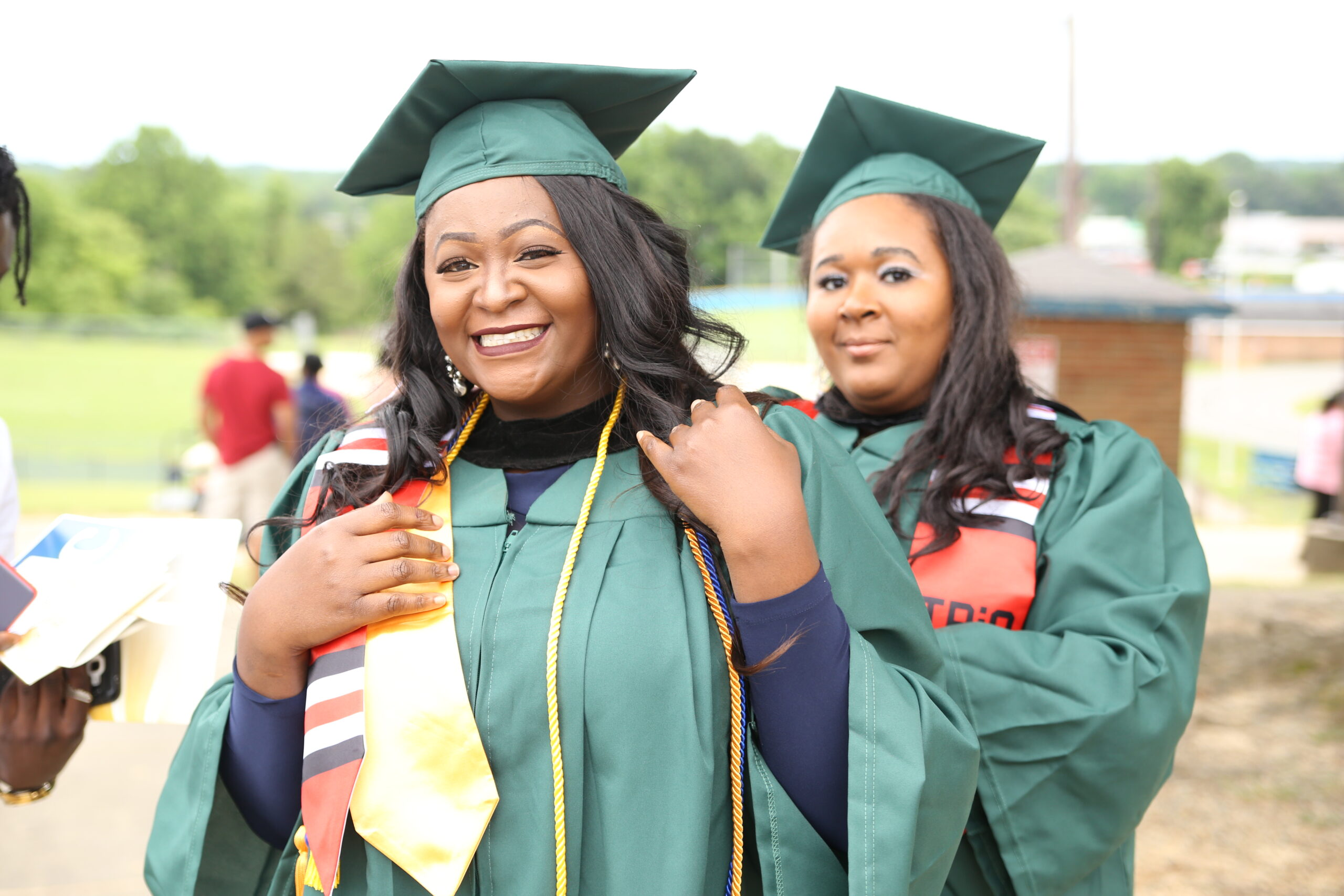 Two black female students in line celebrating their graduation in their dark green cap and gowns