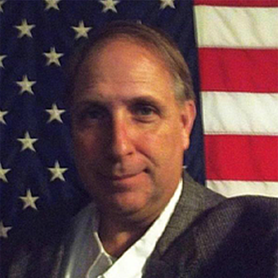 Portrait of Scott Washington in front of American Flag