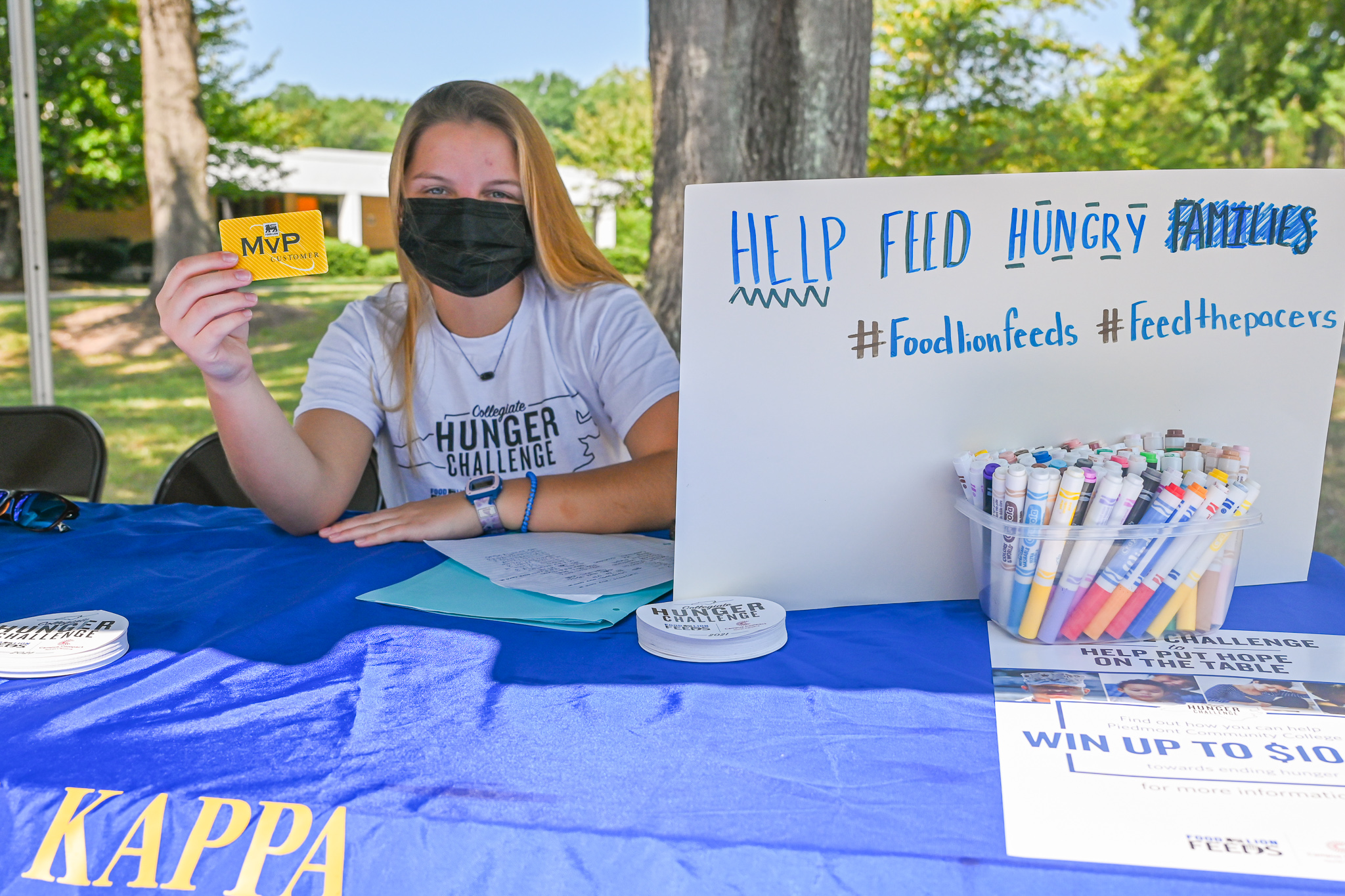 PCC Student Holds Food Lion MVP Card up, with sign dictating how people can help on socials #FoodLionFeeds #FeedThePacers